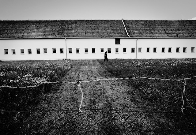 Breclav,Czech Republic. A man walks past rows of windows on a long abandoned stable that's since been converted to a home.  Two years has passed since three roman families, without future prospects were deported to an old converted cow-house outside the town of Breclav in the south of the Czech Republic.